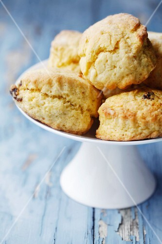 Home-made scones on a white cake stand on a blue wooden surface