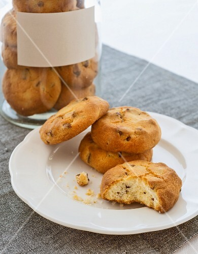 Chocolate chip cookies on a plate and in a storage jar