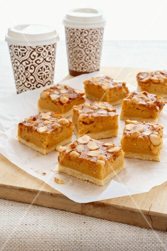 Macadamia nut slices with coffee in takeaway cups