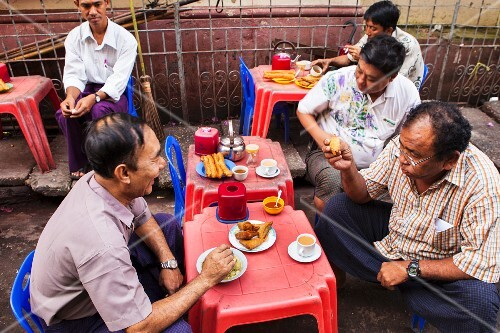 Enjoying samosas and tea in the street, Yangon, Myanmar