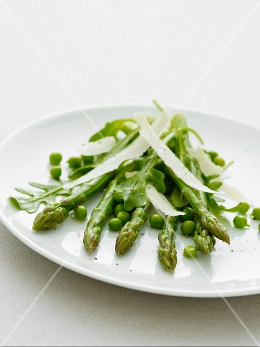 Asparagas and peas with parmesan shavings on a white plate