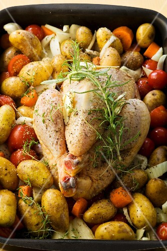 Raw chicken with vegetables in a roasting tin