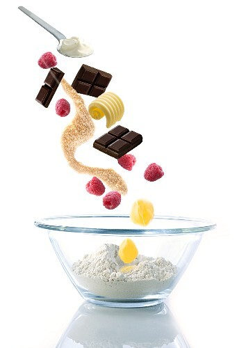 Ingredients for chocolate muffins with raspberries, falling into a glass bowl