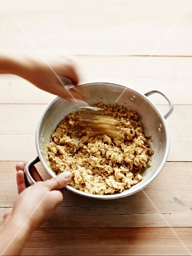 Oat and butter mixture in a metal bowl being stirred by hand
