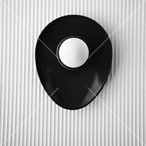 A white egg in a black egg cup, overhead, on a white textured background