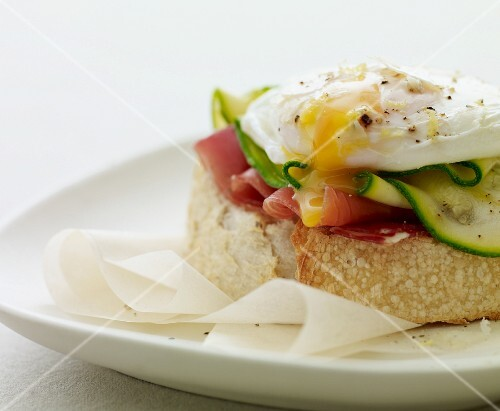 Toasted bread with ham and courgette, topped with a poached egg
