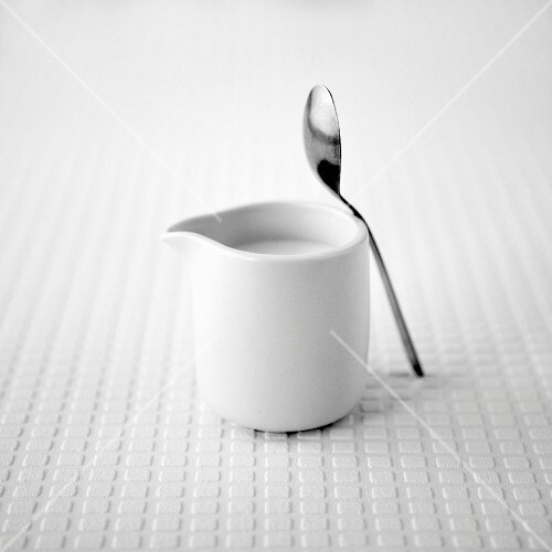 White jug of milk with a teaspoon on a white textured background