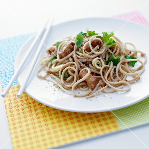 Pad thai with parsley garnish on a white plate with white chopsticks