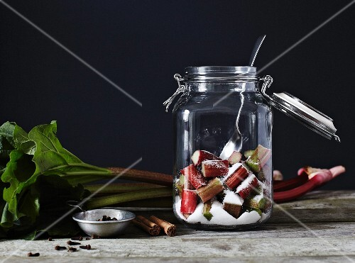 Chopped rhubarb and sugar, in an open kilner jar with a metal spoon
