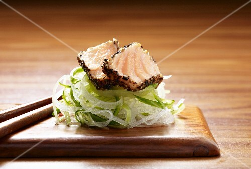 Seared peppered salmon on a bed of daikon and cucumber ribbons