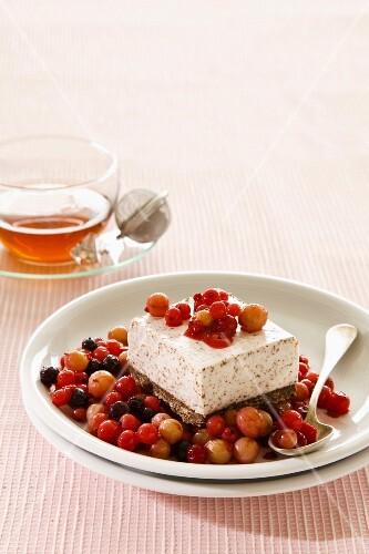 A slice of ice cream cake on stewed berries