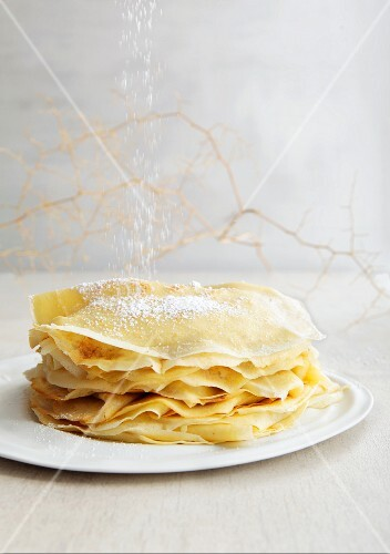 Icing sugar being dusted onto a stack of crepes