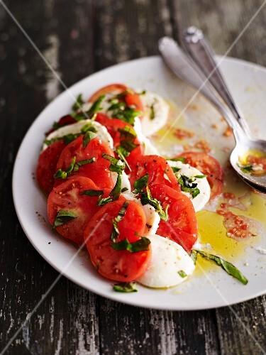 A half-eaten plate of tomato mozzarella salad