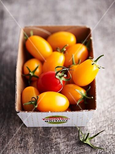 Small yellow tomatoes in a cardboard box