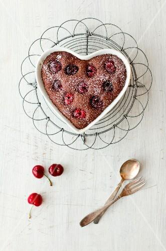 A heart-shaped chocolate and cherry cake