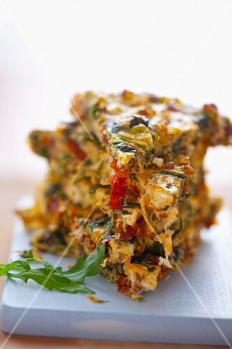 A portion of vegetable frittata with spinach, leek, sundried tomatoes and onions