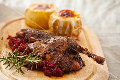 Marinated chicken with cranberry compote; in the background, stuffed butternut squash