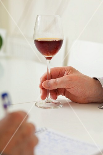 A hand holding a glass of sparkling drink