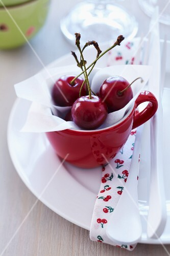 Freshly picked cherries in a red cup on a plate