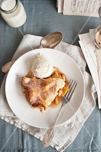 A slice of apple pie with a scoop of vanilla ice cream