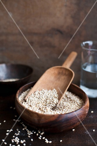 Pearl barley in a wooden bowl with a shovel