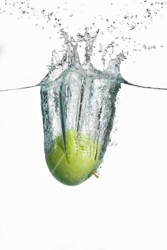 A green apple falling into water