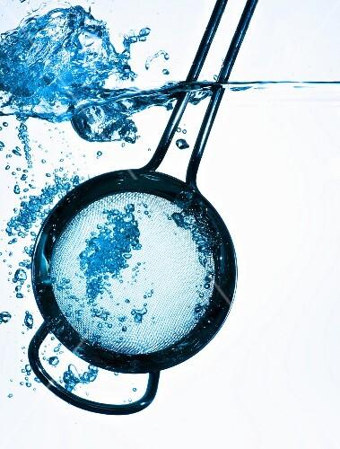 A kitchen sieve in water
