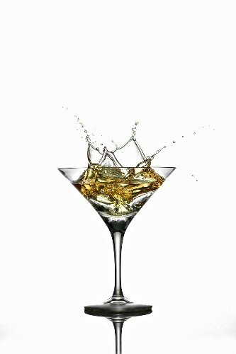A martini splashing out of a glass