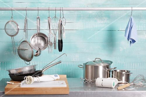 Assorted kitchen utensils on a stainless steel unit and hanging on a metal rod