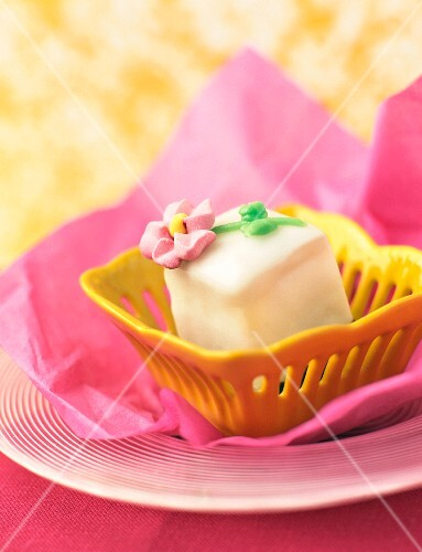 Petit four in a yellow dish on pink paper