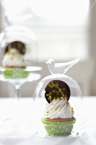A cupcake topped with whipped cream and a giant chocolate button under a glass dome