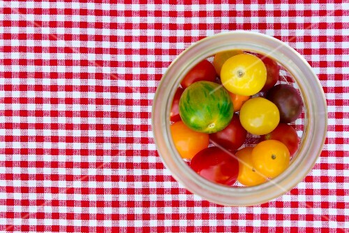 Fresh heirloom tomatoes in a preserving jar on a checked tablecloth