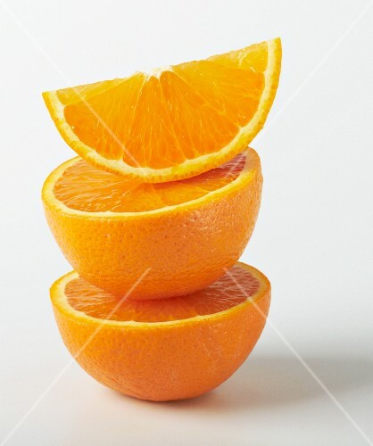 A stack of orange halves and a wedge of orange