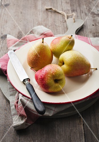 Four pears with water droplets and a knife on a plate
