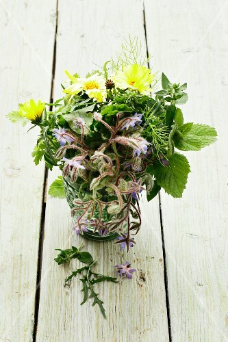 A bunch of herbs with borage and marigolds in a glass of water
