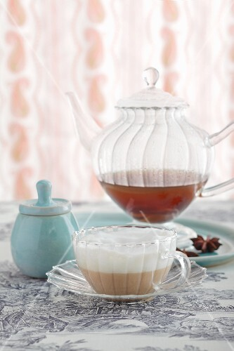 Chai latte in a glass teacup in front of a glass teapot
