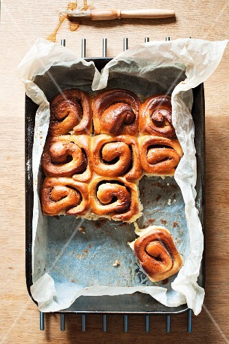Sweet bread rolls in a baking tin with a pastry brush some removed
