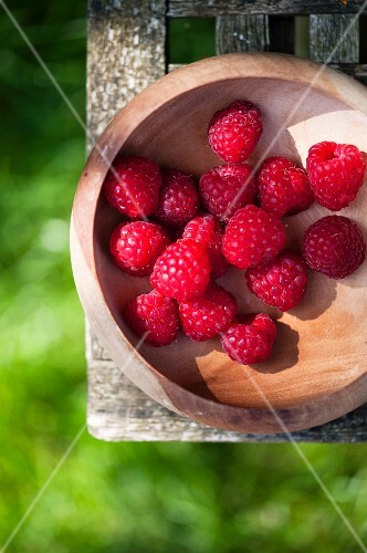 bowl of fresh raspberries on a garden table