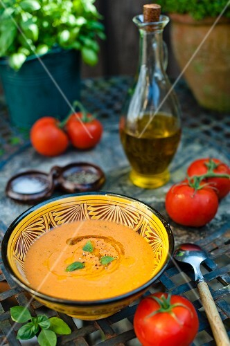 bowl of gazpacho soup on a garden table with fresh tomatoes and olive oil