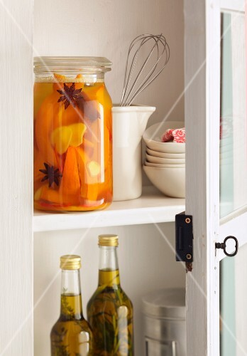 Preserved fruits and kitchen utensils in an open kitchen cupboard