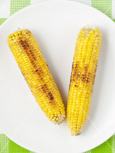 Two barbecued corn cobs on a plate (view from above)
