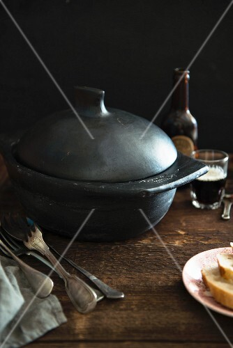 A black cooking pot, silver cutlery, bread and beer on a wooden table (England)