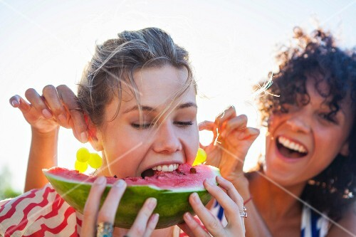 A woman eating a wedge of melon while her friend holds grapes up by her ears as earrings
