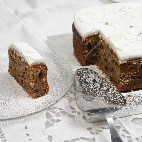 Partly sliced fruit cake with icing
