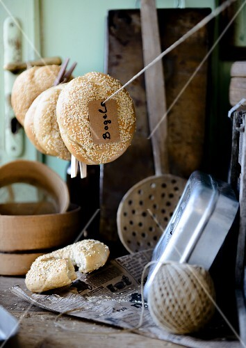 Sesame bagels hanging on a line in a rustic kitchen