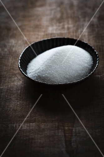 Sugar in a bowl on a wooden table