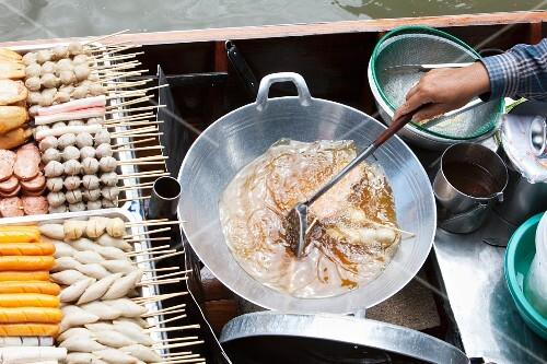 A woman cooking a traditional dish on a boat at the market (Bangkok, Thailand)