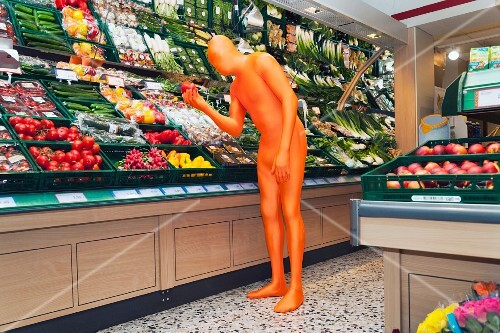 A man in an orange costume looking at a pepper in the supermarket