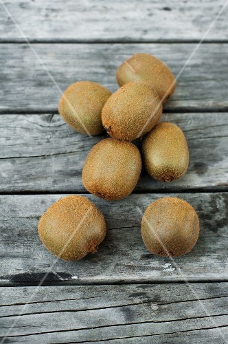 Several kiwi fruit on a wooden surface