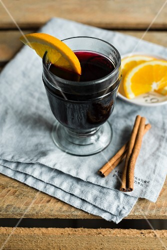 A glass of mulled wine with a slice of orange